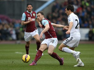 Ashley Barnes of Burnley clears the ball as Jack Cork of Swansea City closes in during the Barclays Premier League match between Burnley and Swansea City at Turf Moor on February 28, 2015