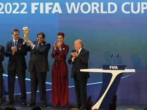 Qatar's Emir Sheikh Hamad bin Khalifa al-Thani (C) raises the World Cup trophy as he stands with FIFA president Sepp Blatter (R) after Qatar was chosen to host the 2022 World Cup at the FIFA headquarters in Zurich on December 2, 2010