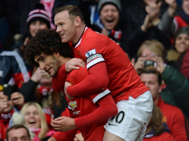 Manchester United's Belgian midfielder Marouane Fellaini celebrates with Manchester United's English striker Wayne Rooney after scoring the opening goal of the English Premier League football match between Manchester United and Tottenham Hotspur at Old Tr