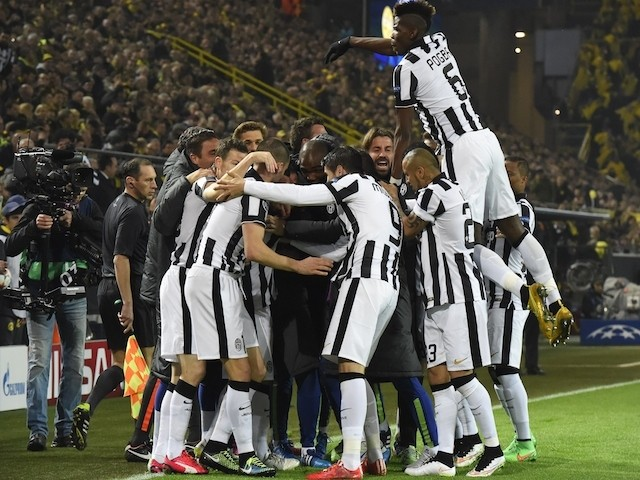 Juventus' Argentinian forward Carlos Tevez (hidden) celebrates scoring with his team-mates scores the 0-1 goal during the Round of 16 second-leg UEFA Champions League football match  against Dortmund on March 18, 2015