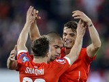 Switzerland's midfielder Granit Xhaka celebrates with teammates midfielder Xherdan Shaqiri (L) and midfielder Gokhan Inler after he scored the team's second goal during the Euro 2016 qualifying football match between Switzerland and Estonia at the Swisspo