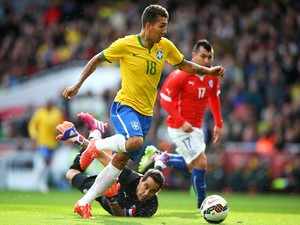Firmino of Brazil rounds goalkeeper Claudio Bravo of Chile to score the opening goal during the international friendly match between Brazil and Chile at the Emirates Stadium on March 29, 2015