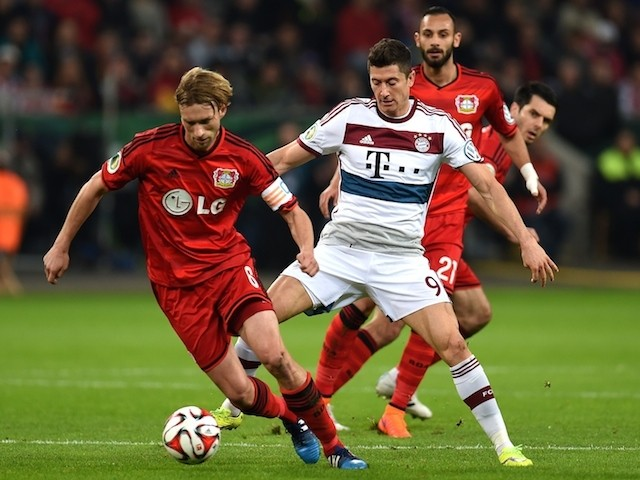 Bayern Munich's Polish striker Robert Lewandowski and Leverkusen's midfielder Simon Rolfes vie for the ball during the German Cup DFB Pokal quarter final football match on April 8, 2015