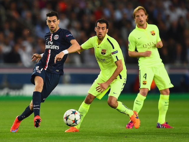 Javier Pastore of PSG is challenged by Sergio Busquets of Barcelona during the UEFA Champions League Quarter Final First Leg match between Paris Saint-Germain and FC Barcelona at Parc des Princes on April 15, 2015