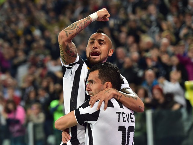 Juventus' forward from Argentina Carlos Tevez celebrates after scoring with Juventus' midfielder from Chile Arturo Vidal during the Italian Serie A football match Juventus vs Lazio at 'Juventus Stadium' in Turin on April 18, 2015