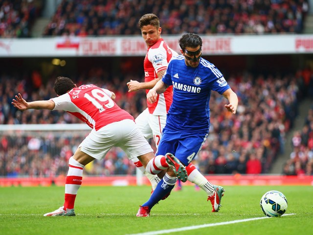 Cesc Fabregas of Chelsea is challenged by Santi Cazorla of Arsenal during the Barclays Premier League match between Arsenal and Chelsea at Emirates Stadium on April 26, 2015