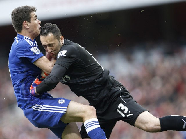 Arsenal's Colombian goalkeeper David Ospina collides with Chelsea's Brazilian midfielder Oscar during the English Premier League football match between Arsenal and Chelsea at the Emirates Stadium in London on April 26, 2015