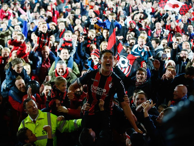 Captain Tommy Elphick of Bournemouth celebrates victory as fans invade the pitch after the Sky Bet Championship match between AFC Bournemouth and Bolton Wanderers at Goldsands Stadium on April 27, 2015