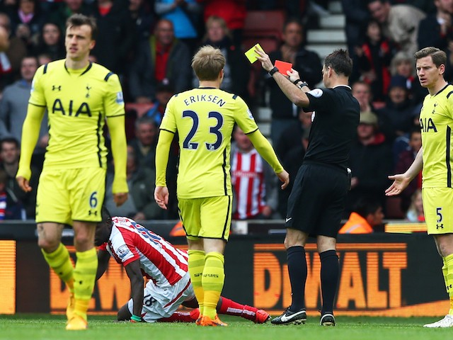 Vlad Chiriches (L) of Tottenham Hotspur leaves the field after being shown the red card by referee Mark Clattenburg during the Barclays Premier League match between Stoke City and Tottenham Hotspur at Britannia Stadium on May 9, 2015