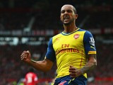 Theo Walcott of Arsenal celebrates as his cross deflects off of Tyler Blackett of Manchester United for an own goal during the Barclays Premier League match between Manchester United and Arsenal at Old Trafford on May 17, 2015