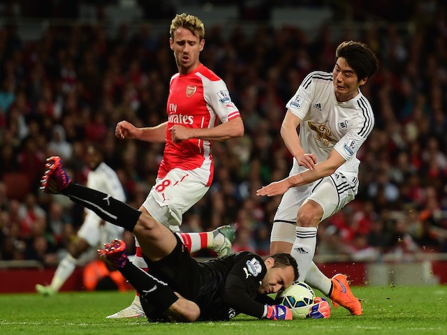 Nacho Monreal of Arsenal looks on as David Ospina of Arsenal makes a save at the feet of Ki Sung-Yueng of Swansea City during the Barclays Premier League match between Arsenal and Swansea City at Emirates Stadium on May 11, 2015