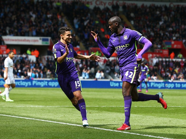 Yaya Toure of Manchester City is congratulated by teammate Jesus Navas of Manchester City after scoring his team's third goal during the Barclays Premier League match between Swansea and Manchester City at the Liberty Stadium on May 17, 2015