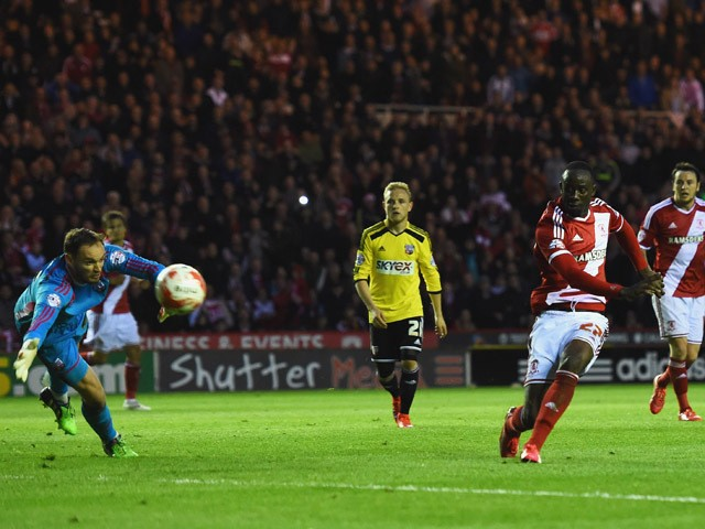 Albert Adomah of Middlesbrough shoots past goalkeeper David Button of Brentford to score their third goal during the Sky Bet Championship Playoff semi final second leg match between Middlesbrough and Brentford at the Riverside Stadium on May 15, 2015