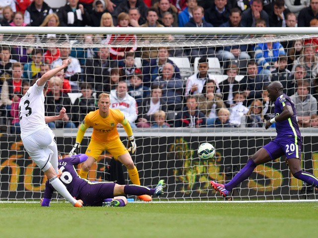 Gylfi Sigurdsson of Swansea City scores a goal despite the challenge from Martin Demichelis of Manchester City during the Barclays Premier League match between Swansea and Manchester City at the Liberty Stadium on May 17, 2015