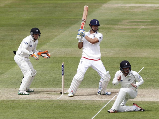 Englands Captain Alastair Cook (2nd L) hits a shot for 4 runs watched by New Zealands wicketkeeper Tom Latham (L) during play on the fourth day of the first cricket Test match between England and New Zealand at Lord's cricket ground in London on May 24, 2