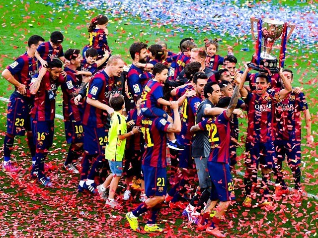 FC Barcelona players celebrate with La Liga trophy at the end of the La Liga match between FC Barcelona and RC Deportivo de la Coruna at Camp Nou on May 23, 2015
