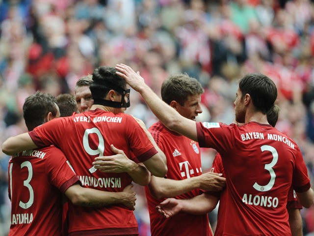 Bayern Munich's Polish striker Robert Lewandowski celebrates scoring with his team-mates during German first division Bundesliga football match FC Bayern Munich vs 1 FSV Mainz 05 at the Allianz Arena in Munich, southern Germany on May 23, 2015