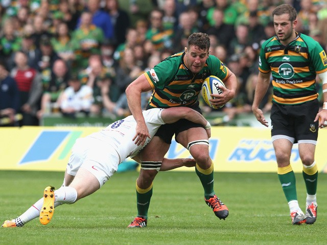 Calum Clark of Northampton is tackled by Owen Farrell during the Aviva Premiership play off semi final match between Northampton Saints and Saracens at Franklin's Gardens on May 23, 2015