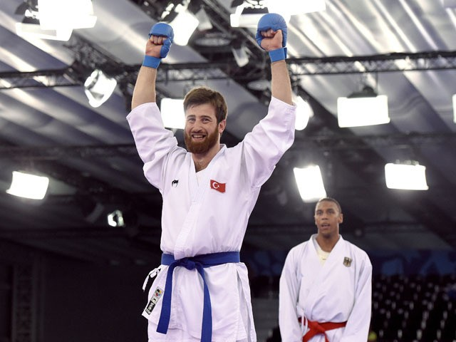 Turkey's Enes Erkan (front) reacts after winning the gold medal after competing against Germany's Jonathan Horne (background) in the Men's Karate Kumite +84kg, during the 2015 European Games in Baku on June 14, 2015