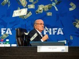 Sepp Blatter is showered in fake money at a FIFA press conference on July 20, 2015