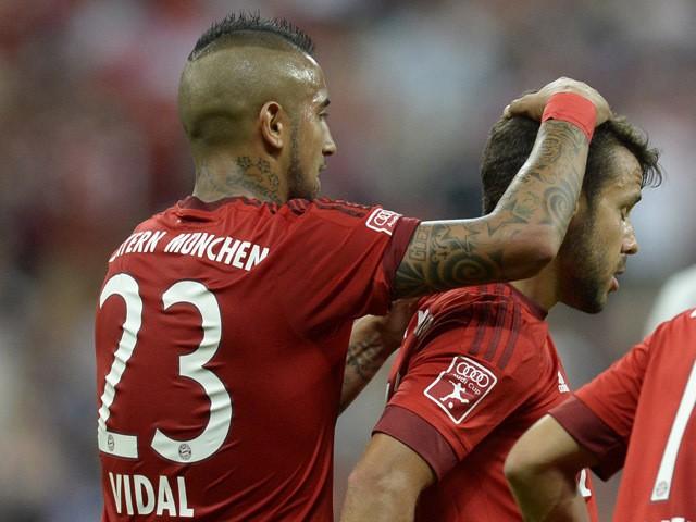 Bayern Munich's Spanish defender Juan Bernat celebrates scoring with Chilean midfielder Arturo Vidal during the Audi Cup football match FC Bayern Munich vs AC Milan in Munich, southern Germany, on August 4, 2015