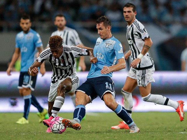 Kingsley Coman of Juventus FC contests the ball against Miroslav Klose of Lazio during the Italian Super Cup final football match between Juventus and Lazio at Shanghai Stadium on August 8, 2015