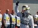 Mercedes AMG Petronas F1 Team's British driver Lewis Hamilton waves after taking the pole position in the pits after the qualifying session at the Spa-Francorchamps ciruit in Spa on August 22, 2015