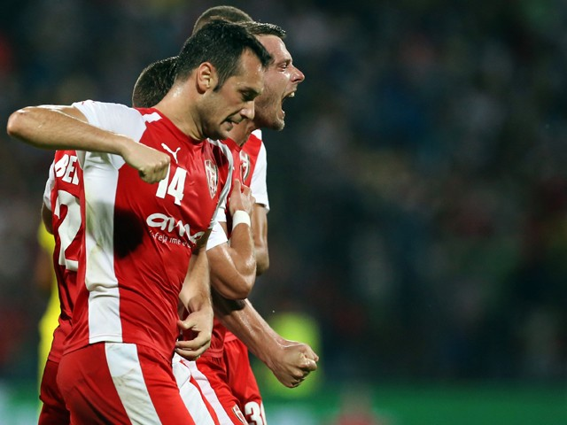 Skenderbeu's Bledi Shkembi (R) and teammates celebrate after the opening goal during the UEFA Champions League playoff football match between KF Skenderbeu and Dinamo Zagreb at the Elbansan Arena in Elbasan, Albania on August 19, 2015