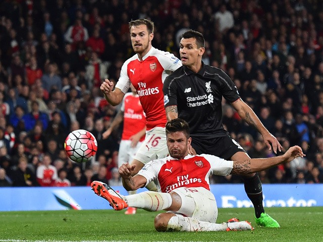 Arsenal's French striker Olivier Giroud has a shot on goal past Liverpool's Croatian defender Dejan Lovren during the English Premier League football match between Arsenal and Liverpool at the Emirates stadium, north London on August 24, 2015