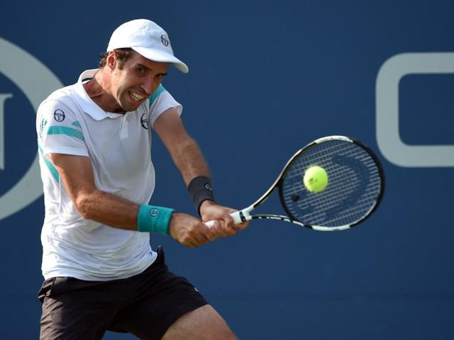Mikhail Kukushkin of Kazakhstan hits shot to Grigor Dimitrov of Bulgaria during their 2015 US Open Men's singles round two match at the USTA Billie Jean King National Tennis Center September 2, 2015