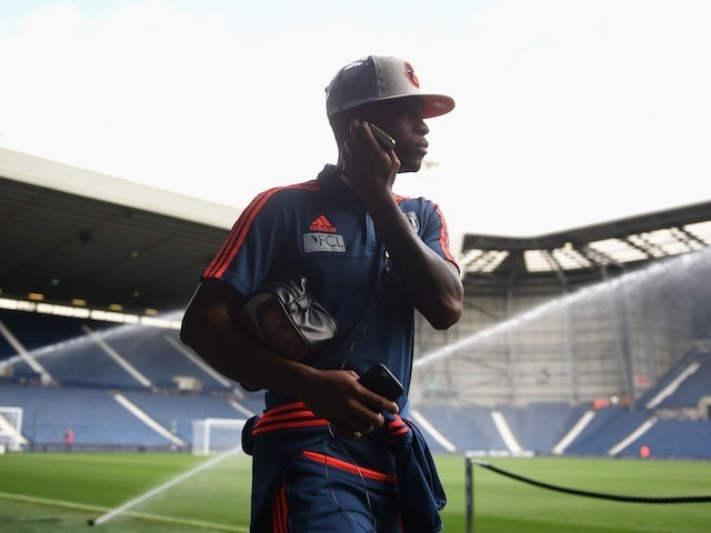 Saido Berahino holds two phones as he arrives at The Hawthorns ahead of West Brom's game with Southampton on September 12, 2015