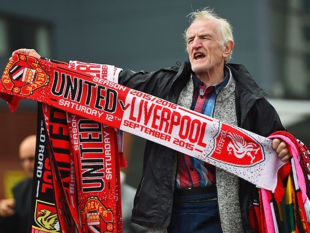 An elderly gentleman flogs two scarves for a tenner outside Old Trafford ahead of the game between Manchester United and Liverpool on September 12, 2015