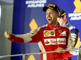 Sebastian Vettel of Germany and Ferrari celebrates on the podium after winning the Formula One Grand Prix of Singapore at Marina Bay Street Circuit on September 20, 2015