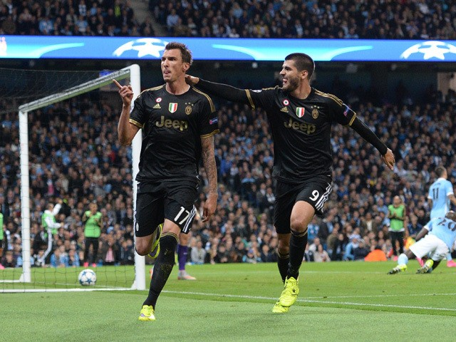 Juventus' forward from Croatia Mario Mandzukic (L) celebrates with Juventus' forward from Spain Alvaro Morata after scoring during a UEFA Champions League group stage football match between Manchester City and Juventus at the Etihad stadium in Manchester,