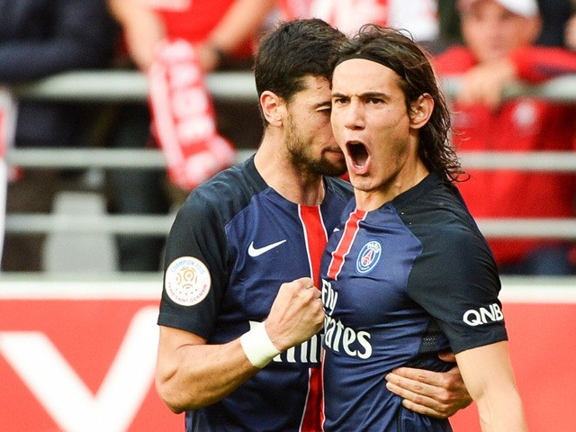 Paris Saint-Germain's Uruguayan forward Edinson Cavani is congratulated by his teammate on scoring during the French Ligue 1 football match between Reims and Paris Saint-Germain on September 19, 2015