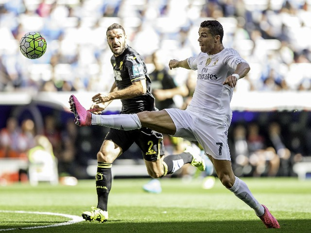 Cristiano Ronaldo (R) of Real Madrid CF competes for the ball with David Rodriguez Lomban (L) of Granada CF during the La Liga match between Real Madrid CF and Granada CF at Estadio Santiago Bernabeu on September 19, 2015 in Madrid, Spain.