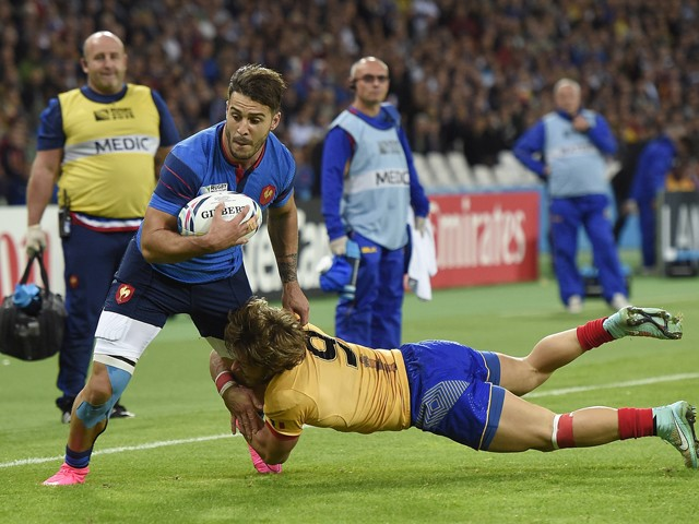 France's wing Sofiane Guitoune (L) is tackled by Romania's scrum half Florin Surugiu as he runs to score a try during a Pool D match of the 2015 Rugby World Cup between France and Romania at the Olympic stadium, east London, on September 23, 2015