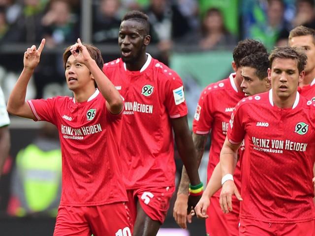 Hannover 96 players celebrate after Hanover's Japanese midfielder Hiroshi Kiyotake (L) scored during the German first division Bundesliga football match VfL Wolfsburg vs Hannover 96 in Wolfsburg, northern Germany, on September 26, 2015