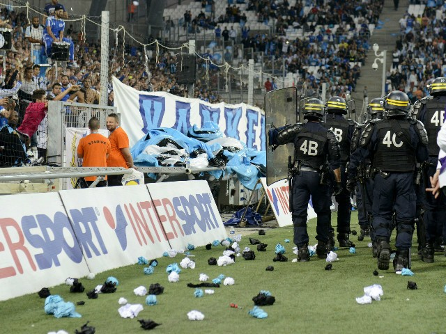 In this picture taken on September 20, 2015 riot police patrol around the touchline after crowd trouble during the French L1 football match Marseille (OM) vs Lyon (OL) at the Velodrome Stadium in Marseille, southern France. Play was resumed after an inter