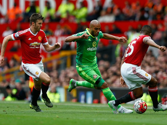 Younes Kaboul (C) of Sunderland competes against Michael Carrick (L) and Antonio Valencia (R) of Manchester United during the Barclays Premier League match between Manchester United and Sunderland at Old Trafford on September 26, 2015 in Manchester, Unite