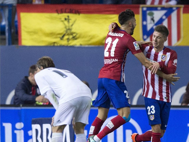 Luciano Dario Vietto (R) of Atletico de Madrid celebrates scoring their opening goal with teammate Yannick Carrasco (2ndR) as Luka Modric (R) of Real Madrid CF recats during the La Liga match between Club Atletico de Madrid and Real Madrid CF at Vicente C
