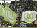 Snow falls as Wolfsburg flags are waved by fans next to the pitch ahead of the German first division Bundesliga football VfL Wolfsburg vs Borussia Dortmund in the northern German city of Wolfsburg on April 7, 2012