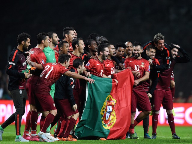 Portugal's players celebrate as they pose with a Portuguese flag at the end of the Euro 2016 qualifying football match Portugal vs Denmark at the Municipal stadium in Braga on October 8, 2015.