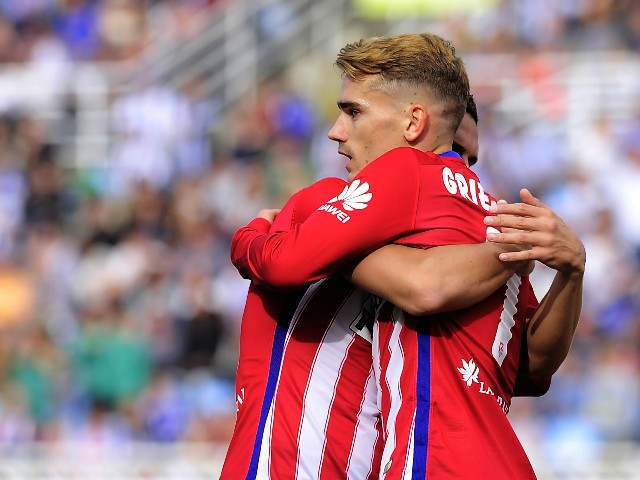 Atletico Madrid's French forward Antoine Griezmann (R) is congratulated by teammate midfielder Koke (L) after scoring during the Spanish league football match Real Sociedad de Futbol vs Club Atletico de Madrid at the Anoeta stadium in San Sebastian on Oct