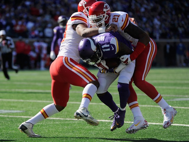 Ramik Wilson #53 and Sean Smith #21 of the Kansas City Chiefs stop the progress of Mike Wallace #11 of the Minnesota Vikings during the first quarter of the game on October 18, 2015