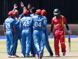 Afghan players celebrate next to Zimbabwe's Chamunorwa Chibhabha (R) during the final game in a series of five ODI cricket matches between Afghanistan and hosts Zimbabwe at Queens Sports Club, in Bulawyo, on October 24, 2015.