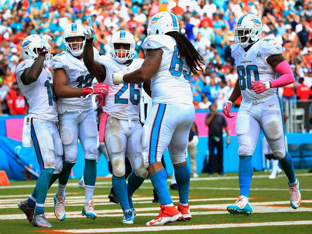 Lamar Miller #26 of the Miami Dolphins celebrates his touchdown with his teammates in the second quarter against the Houston Texans at Sun Life Stadium on October 25, 2015
