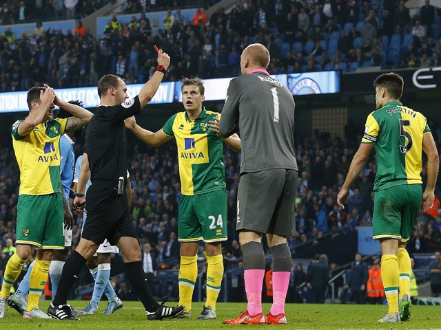 Referee Robert Madley shows Norwich City's Scottish defender Russell Martin (R) a red card during the English Premier League football match between Manchester City and Norwich City at The Etihad Stadium in Manchester, north west England on October 31, 201
