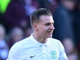 Jason Cummings of Hibernian is shown a yellow card by referee Steven McLean after celebrating scoring the opening goal with his team-mates in front of the Hearts fans in the first half during the Scottish Championship match between Heart of Midlothian F.C
