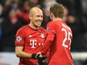 Bayern Munich's Dutch midfielder Arjen Robben (L) and Bayern Munich's striker Thomas Mueller (R) react after the second goal for Munich during the UEFA Champions League Group F football match between FCB Bayern Munich and Olympiakos Piraeus on November 24